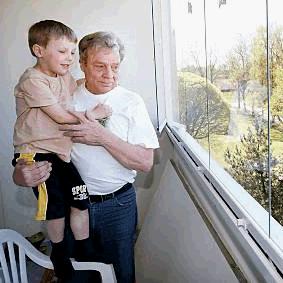 Мальчик Антон с папой Пааво смотрят с балкона на майскую природу. Фото Юхи Синисало »Lehtikuva»